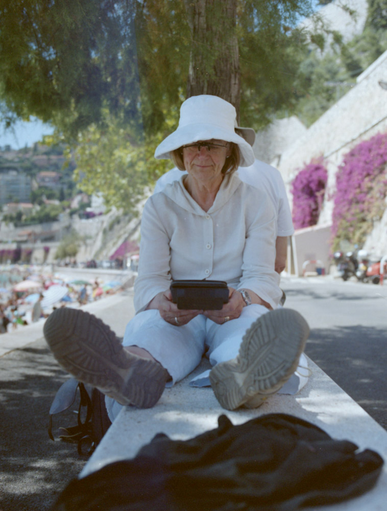 woman enjoying the sun with her kindle at the beach of Villefranche | by bertram rusch